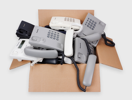 corded: VILNIUS, LITHUANIA - JANUARY 25, 2016: A cardboard box with Panasonic cheap phones which are prepared for utilization and processing. Cost of one phone about 10 euros