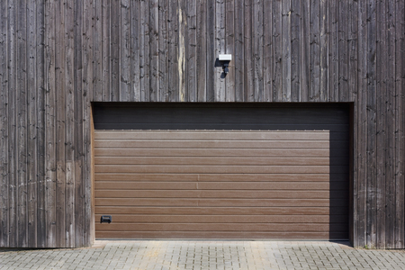 motion sensor: Wooden wall of modern rural garage with the automatic lifted gate. The motion sensor and the alarm system on a wall over an entrance
