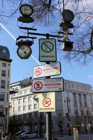 forbidding: VILNIUS, LITHUANIA - MARCH 13, 2016:  Surveillance cameras and the forbidding banners on Gediminas Avenue. Inscriptions on Lithuanian - are forbidden to be smoked, the skateboard, alcohol, to litter