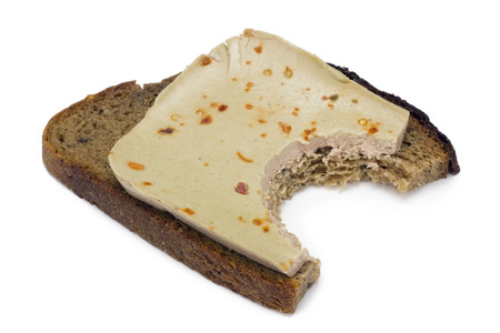 are taken: The taken a bite sandwich from black bread and liver pate lies on a white table.