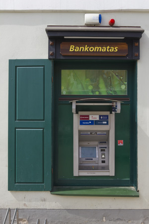 automatic transaction machine: VILNIUS, LITHUANIA - MAY 04, 2013: The street ATM  is built in in a simple wooden window of DNB  bank. In Norway, DNB has more than 2.3 million retail customers and more than 200,000 corporate clients, with 218 Branch offices.
