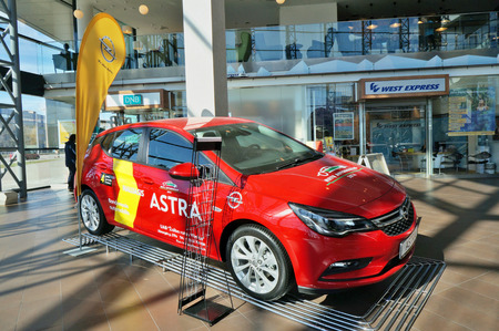 astra: VILNIUS, LITHUANIA - APRIL 02, 2016: Demonstration of new model of the red car Opel Astra in the largest shopping center Panorama. The producer gives a guarantee on the car of 4 years. Sunny spring morning Editorial