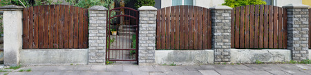 no name: The simple fence of the old no name European house is made of vertical brown thin pine  boards. Columns from a decorative white brick. Sunny spring day panoramic landscape Stock Photo