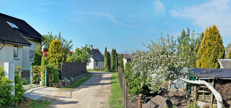 no name: Early spring solar morning in no name European village. Apple trees and cherries have already faded. Panoramic collage from several photos Stock Photo