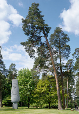centenary: VILNIUS, LITHUANIA - MAY 20, 2016: Symbolical abstract sculpture - Tree of Unity of the Nation of the sculptor of Gutauskas - has been established in 2009  in Vingis public park. Nearby - centenary old curves pines