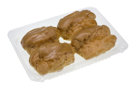 parch: Four  Eclair cakes with scalded carmel and coffee butter cream in standard plastic packing box. Isolated wit parch