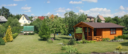 VILNIUS, LITHUANIA - JUNE 18, 2016: Standard garden lodges in rural style and peonies flowers beds in public garden association Kalorija near the Lithuanian village of Rastenenai. Sunny June day
