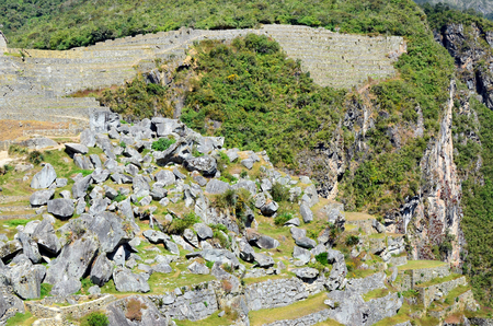 In one photo it is possible to see all history of the Peruvian Andes mountains. Huge granite boulders. Green tropical bushes and trees. Ruins of the ancient stone settlement of the  Inca empire