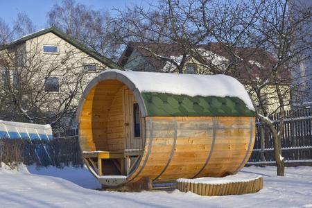 Vilnius, Litauen - 2. Januar 2016: Beliebte ländlichen mobilen Holz Bad in Form eines Fasses in einem Winter rustikalen Garten. Die durchschnittlichen Kosten eines solchen Bades beträgt etwa 1700 ?