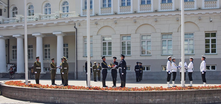 raise the white flag: VILNIUS, LITHUANIA - MAY 29, 2016: Soldiers and seamen of armed forces and navy of the Republic of Lithuania prepare for solemn raising of national flags near the presidential palace