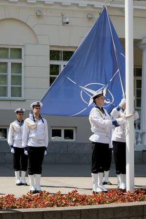 raise the white flag: VILNIUS, LITHUANIA - MAY 29, 2016: Seamens of armed forces and navy of the Republic of Lithuania prepare for solemn raising of NATO flag near the presidential palace