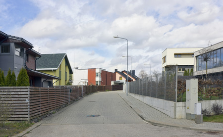 allocated: VILNIUS, LITHUANIA - APRIL 17, 2016: The new from concrete tiles road and private inhabited cottages on rural Angelavos Street (Near angels). Money for construction of the road was allocated by the European Union Editorial