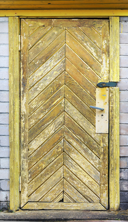 old wooden door: Old wooden door of a rural brick shed. Yellow paint is removed by means of hot air. Expectation of a sunny day for painting.