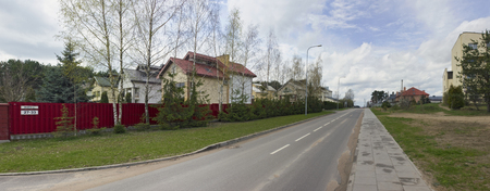allocated: VILNIUS, LITHUANIA - APRIL 17, 2016: The new asphalt road and private inhabited cottages on rural Salotes Street (Lime color). Money for construction of the road was allocated by the European Union