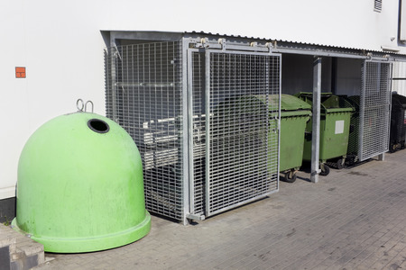 food waste: Tanks for food waste near a supermarket. Steel lattices protect containers from hungry beggars and bums.