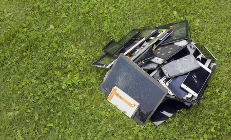 Big heap of the  broken and cracked  cellular telephons and  tablets lie on green lawn grass. Modern technologies pollute environment copncept. There is a place for your text Standard-Bild