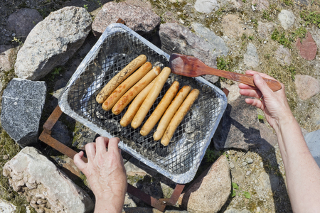 overturn: Process of real frying of pork sausages on a disposable coal Chinese grill. Hands overturn meat a wooden rake. Top view. Sunny summer day