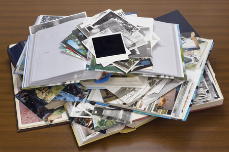 old desk: Nostalgia by youth - old family photo albums and photos lie a heap on a wooden table. Stock Photo