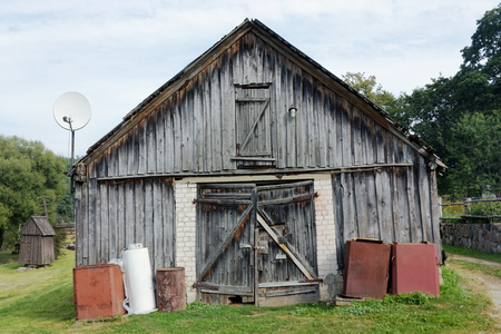 no name: Creative wooden no name rural shed with with the satellite antenna on a roof. Rustic summer landscape Stock Photo