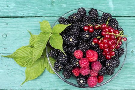 Wild black and red forest  berries lie on green wooden rusric table. Top view background Stock Photo