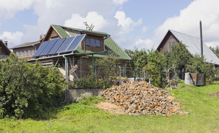 solar heating: For heating and production of hot water in the rural house it is possible to use burning of firewood or the collector of a solar heat. Conceptual rustic landscape Stock Photo
