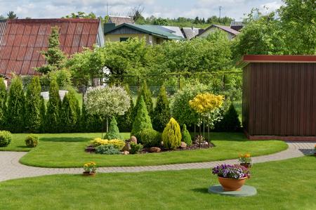 Een deel van een ideale Europese decoratieve landelijke tuin met een groen gazon, bloemen en struiken. Zonnige dag zomer landschap
