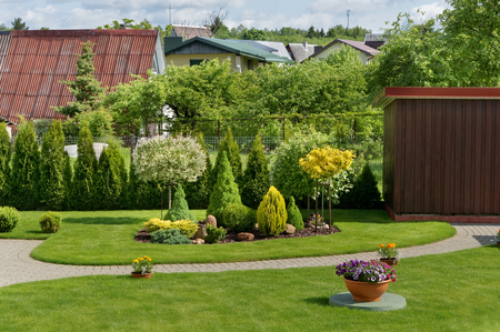 Part of an ideal European decorative rural garden with a green lawn, flowers and bushes. Sunny day summer landscape