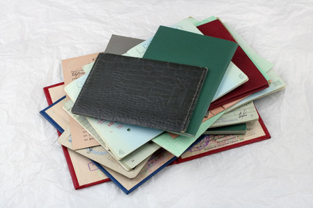 validez: VILNIUS,  LITHUANIA - DECEMBER 16, 2016:  Ancient old personal documentsb lie on vintage white paper, validity period left at the middle of the twentieth century. These are passports, diplomas, the driving license and other.