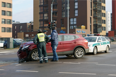 questioned: VILNIUS, LITHUANIA - NOVEMBER 19, 2016:  Police officers are studying the place car accident at the intersection and questioned the driver of the car