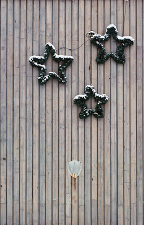 guirnaldas de navidad: Three simple pine Christmas wreaths hang on a vertical wooden wall of rural home. Cloudy day