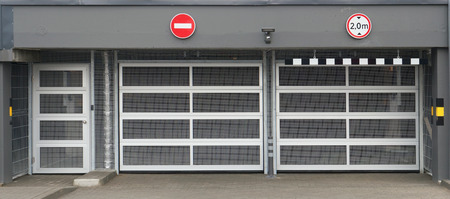 standard steel: Absolutely new and modern standard no name steel mesh gates  in underground automobile garages and a parking. Stock Photo