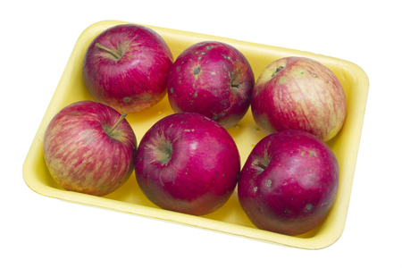 Cheap red ugly apples of the lowest price category for poor people in yellow plastic container. Isolated with patch