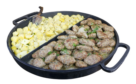 Schnitzels and boiled potatoes with parsley  in a huge frying pan for the big company. Isolated