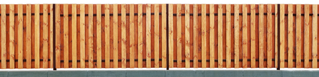 New modern  yellow wooden rural fence from vanished vertical pine planks. Isolated on white with patch. Panoramic collage from several outdoor photos
