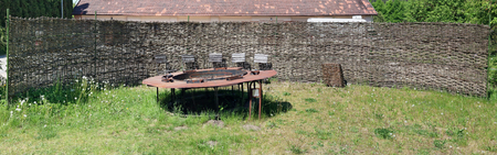 The rural fence from dry reed surrounds the abandoned place for frying of a barbecue. Rusty metal brazier and rotten chairs. Panoramic collage from several photos. Sunny spring day