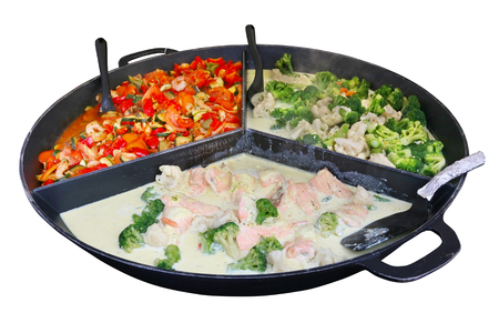 Fast street food - salmon stakes  in creamy sauce with red paprika, shrimp and cabbage in big steel frying pan. Isolated Stock Photo
