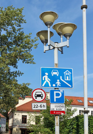 Road signs of the red urban automotive zone hang on a street lamp. Summer sunny day outdoor shot