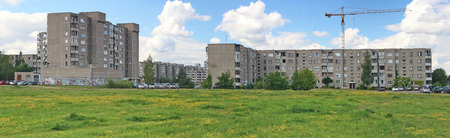 VILNIUS, LITHUANIA - AUGUST 15, 2017:  Big green empty grass lawn  opposite to the huge simple ugly  mass production homes in Pilaite area. The construction of the district began in 1990