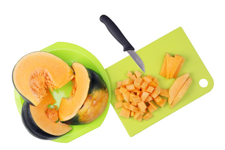 To cook a tasty vegetable soup pumpkin  must be finely chopped into small cubes. Isolated on white top view shot