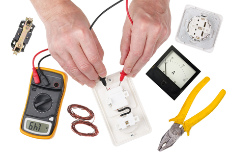 An professional technican  electrican  checks the isolation of the light switch using a multimeter. Isolated on white top view studio shot Stockfoto