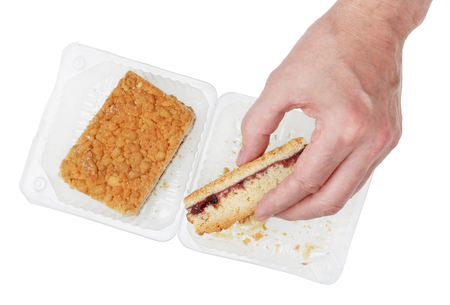 An elderly man takes a piece of sweet  shorty cake from a plastic container.  So many little crumbs. Isolated on white studio top view concept Stock Photo