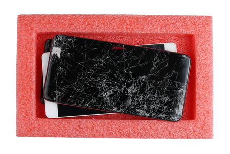 Broken defective smartphones are waiting for their repair in a plastic red industrial box. Isolated on white top view concept studio shot