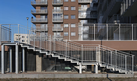 A silver metal ramp and stairs for wheelchairs in a mass production city house where people with disabilities live.