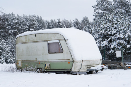 Broken tourist car trailer covered  with snow in the winter forest landscape Stock Photo