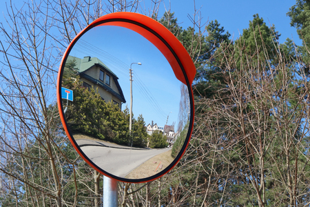 A round convex mirror is installed at the village crossroads for safety. Sunny spring day landscape
