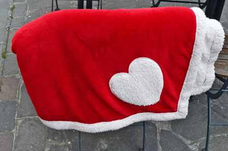 A warm red blanket hangs on a bench in a public park. Any freezing tourist can use it to keep warm.