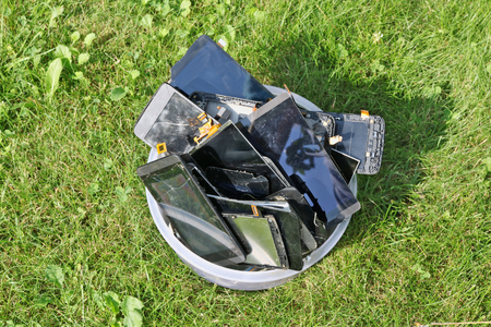 Heap of the  broken and cracked  cellular telephones in plastic box lie on green lawn grass.