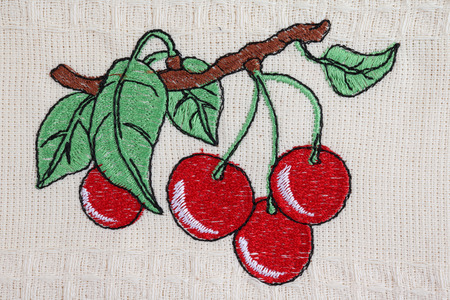 VILNIUS, LITHUANIA - JULY 19, 2018: Homemade simple embroidery of colored threads on canvas in the national Ukrainian style - red cherry fruits