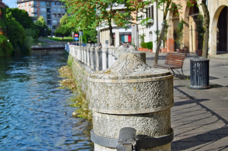 Stone granite  embankment of a small no name Italian city concept. Sunny summer June evening shot.