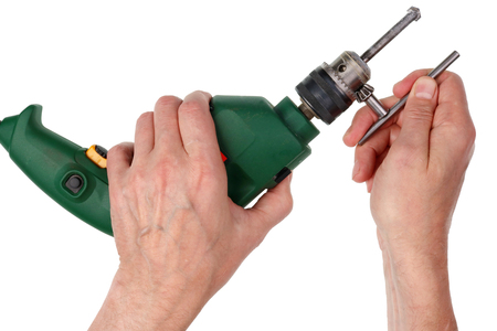 Elderly male home master replaces drill in comact electric drilling machine. Isolated on white studio closeup